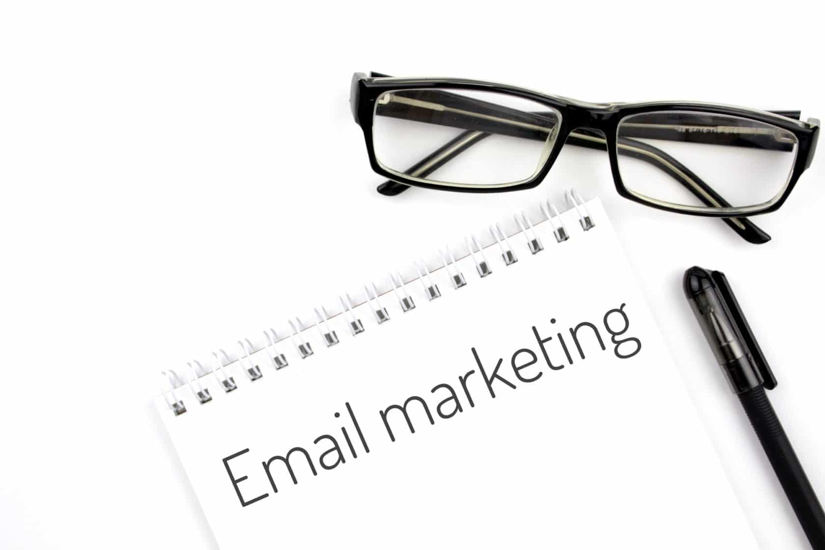 Reading glasses and notebook with word email marketing on a white background