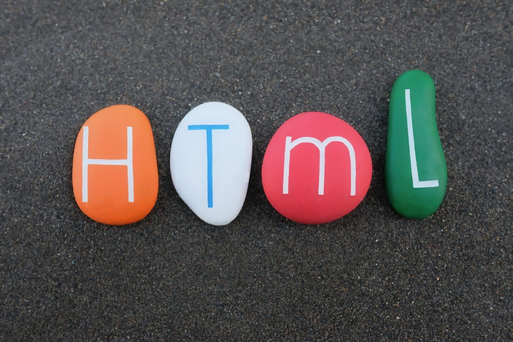 HTML, Hypertext Markup Language composed with colored stones over black volcanic sand