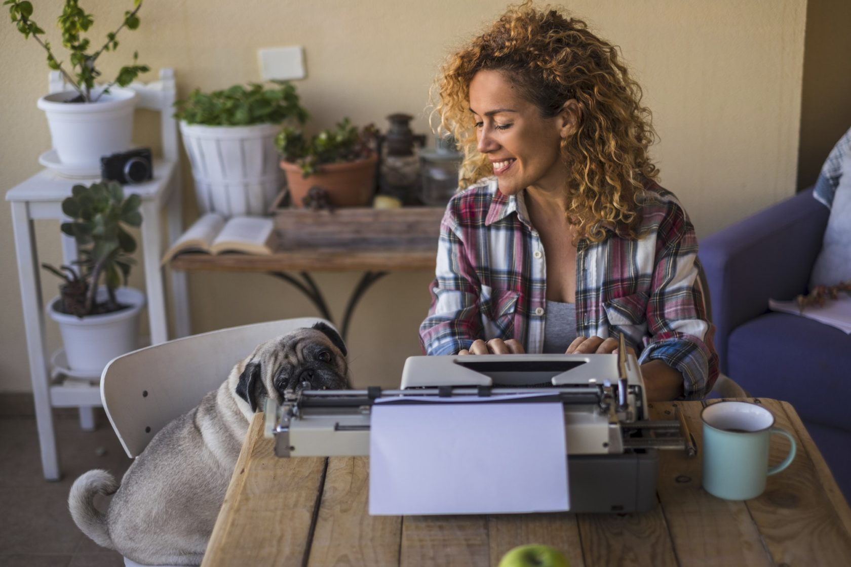 Middle age pretty caucasian woman use an old typewriter to write a blog or book