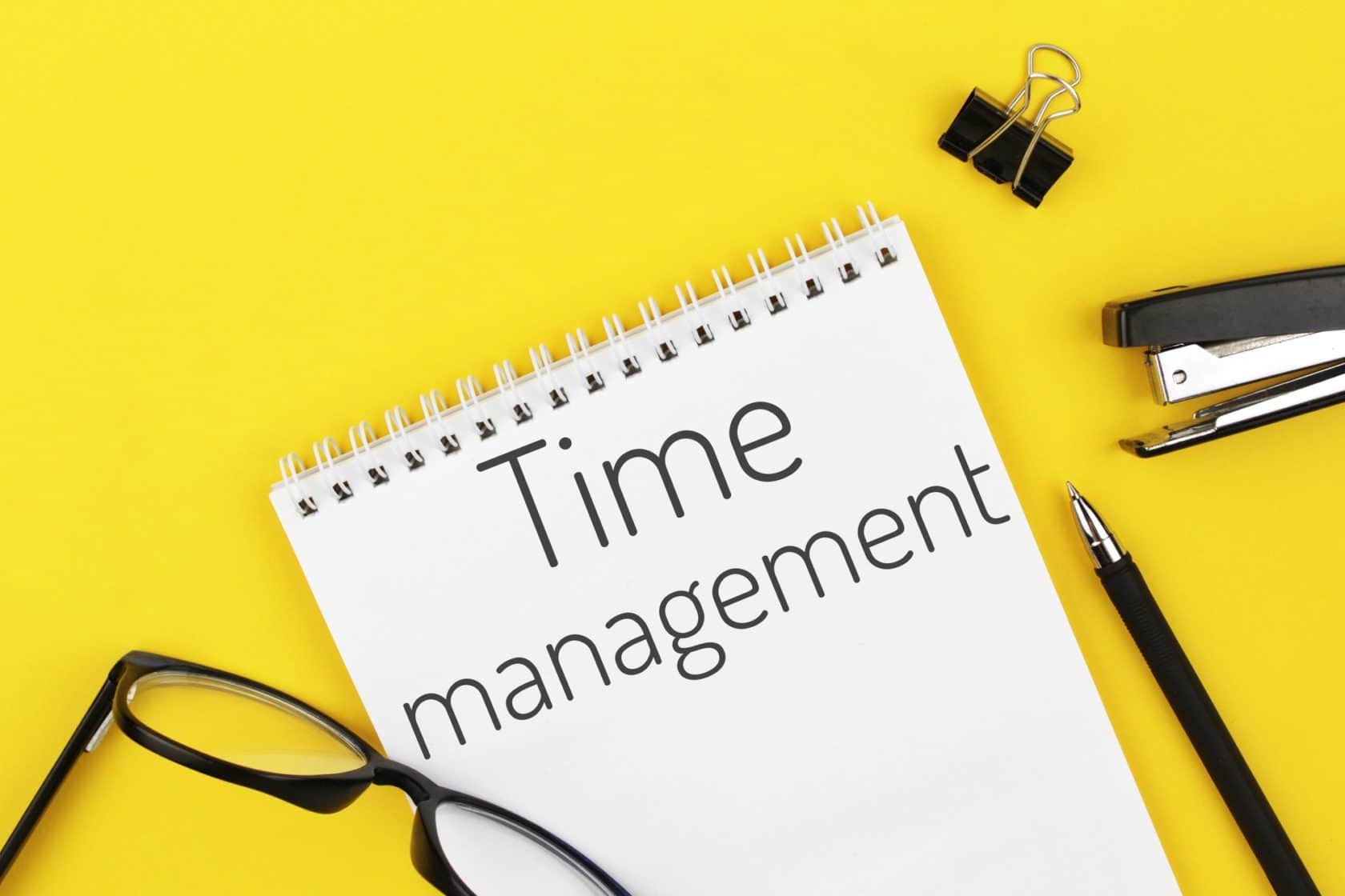 notebook with word time management on a yellow background