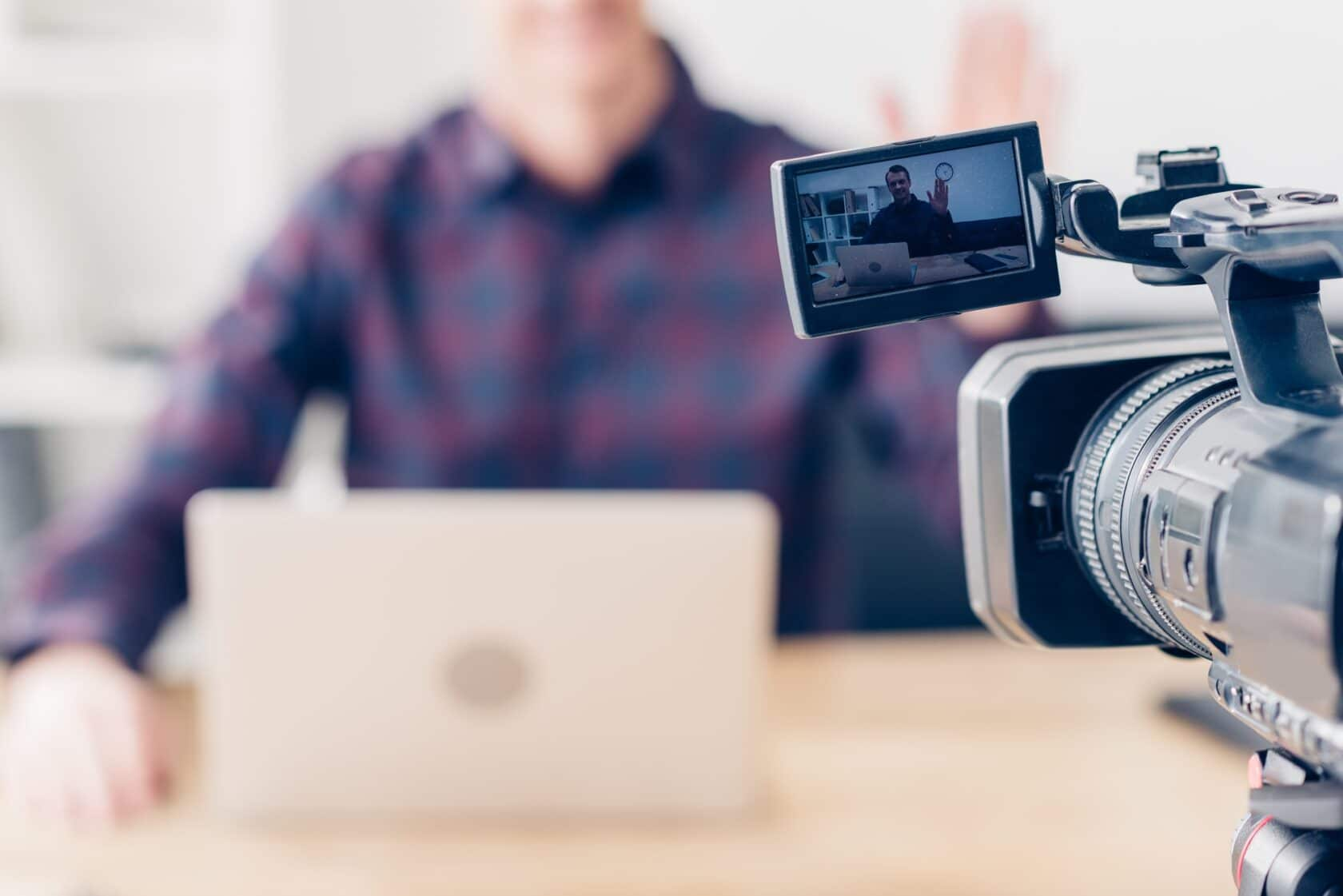 cropped image of male video blogger recording vlog in office, camera on foreground