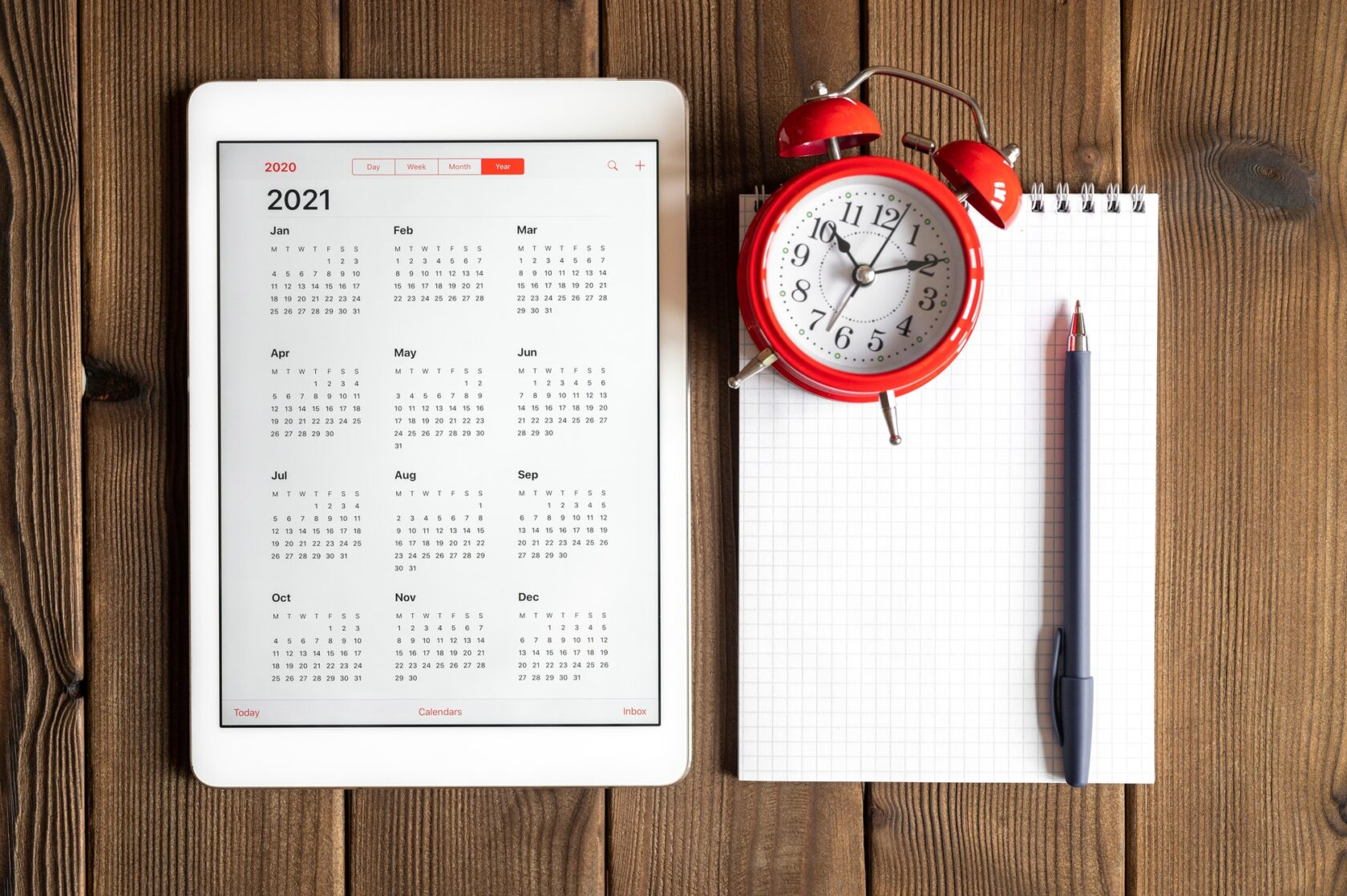 tablet with calendar for 2021, alarm clock and a spring notebook on a wooden background flat lay
